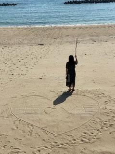 女性,自然,海,LOVE,海水浴,屋外,砂,ビーチ,後ろ姿,砂浜,水面,海岸,手持ち,ハート,人物,人,旅行,旅,棒,ポートレート,ラブ,手書き,佇む,ライフスタイル,手元