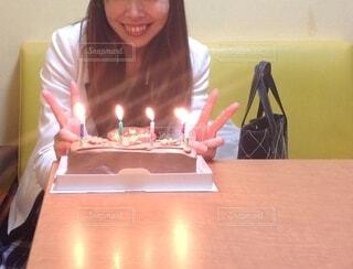 ろうそくに火をつけたバースデーケーキを持つテーブルに座っている女性の写真・画像素材[3822330]