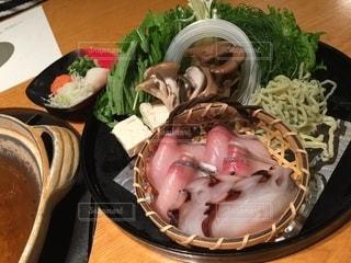 木製のテーブルの上に座っている食べ物のボウルの写真・画像素材[2733839]