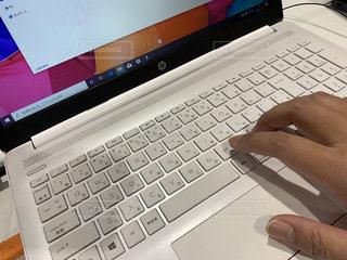 ラップトップコンピュータのキーボードに座っている人の写真・画像素材[2964284]