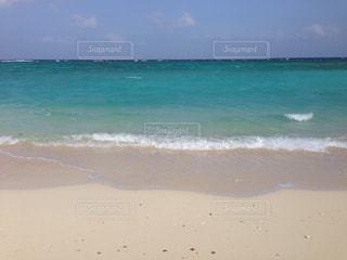 海の隣の砂浜の上に立っている男の写真・画像素材[2994200]