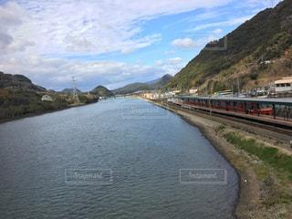水の体の隣の線路を下って移動する列車の写真・画像素材[3010966]