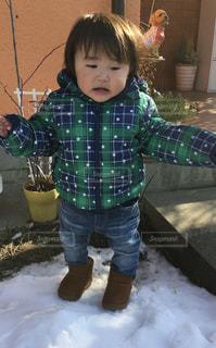 雪の上に立っている小さな男の子の写真・画像素材[2702672]