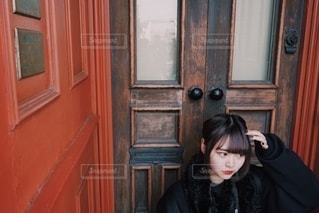 木製のドアに座っている人の写真・画像素材[2697048]
