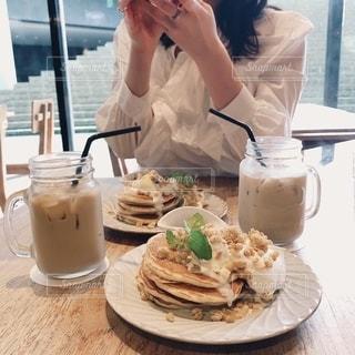 食べ物を食べているテーブルに座っている女性の写真・画像素材[2733926]