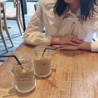 コーヒーを飲みながらテーブルに座っている女性の写真・画像素材[2733937]