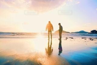 夕日を背景にビーチに立つ男の写真・画像素材[2795286]