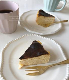 コーヒーを一杯のそばの皿の上に置いたケーキの写真・画像素材[3195685]