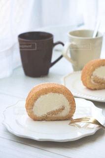 コーヒーを一杯のそばの皿の上に置いたケーキの写真・画像素材[3255915]