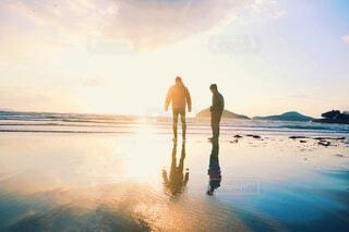 水の体の近くのビーチに立っている男の写真・画像素材[4414796]