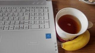 キーボードの隣に座っているコーヒーを一杯の写真・画像素材[3214593]