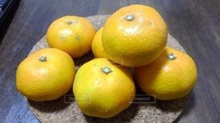 木のテーブルの上に座っている2つのオレンジの写真・画像素材[3905458]