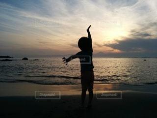 夕日の砂浜と男の子の写真・画像素材[2635770]