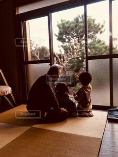 窓の外を眺めるじいじと孫の写真・画像素材[2846145]