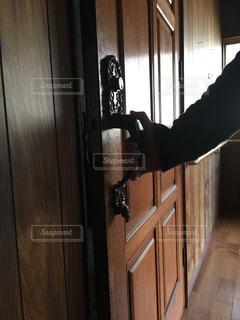 木製のドアを開けている男の写真・画像素材[2871344]