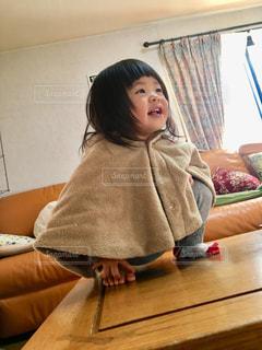 テーブルの上に乗っている女の子の写真・画像素材[2871350]