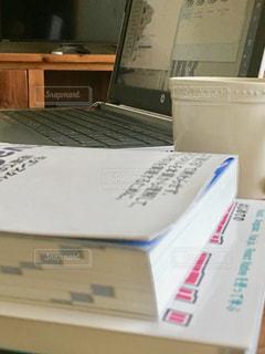 机の上に座っている本とノートパソコンの写真・画像素材[2963423]