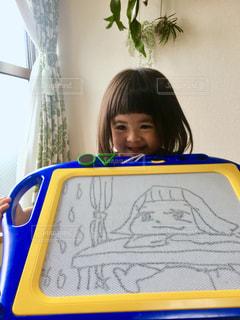お絵かきで微笑んでいる少女の写真・画像素材[3173833]