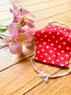 木製の床上にピンクの花とマスクの写真・画像素材[3278107]