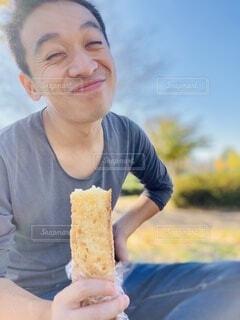 パンを食べて笑顔の男性の写真・画像素材[4025786]