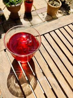 木製のテーブルの上の赤いドリンクの写真・画像素材[4331824]