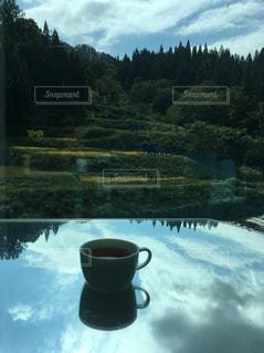鏡張りのテーブルに映る空とティーカップの写真・画像素材[2692216]