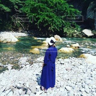 秋の河原で佇む60歳の日本人女性の写真・画像素材[3696291]