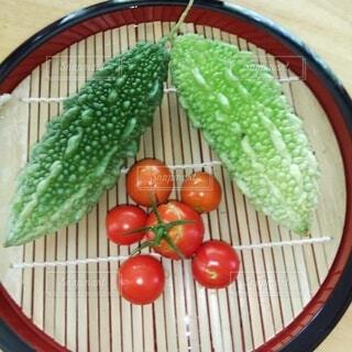 家庭菜園で採れた無農薬のゴーヤとミニトマトの写真・画像素材[3699112]