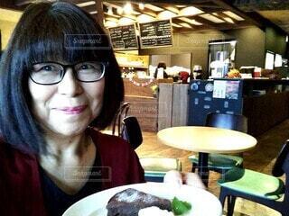 おしゃれなお店でケーキに微笑む60歳の女性の写真・画像素材[3761173]