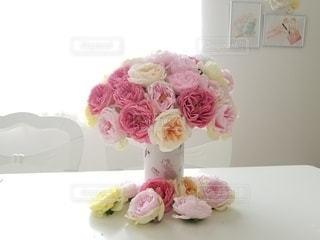 テーブルの上にピンクの花で満たされた白い花瓶の写真・画像素材[3107357]