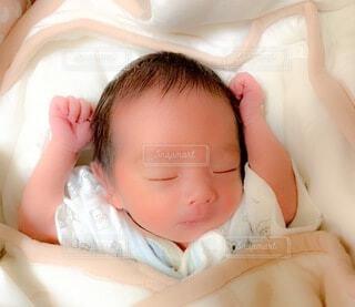 バンザイして寝てる我が子の写真・画像素材[4015497]