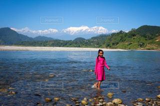 友人の娘。ヒマラヤ山脈をバックに川で遊ぶ。の写真・画像素材[1138570]
