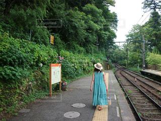 木々を背景に駅のホームに立っている人の写真・画像素材[2820139]