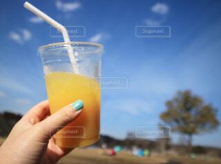 空,ジュース,青空,手,オレンジ,手持ち,ピクニック,人物,人,ポートレート,暮らし,ドリンク,ライフスタイル,手元,飲料,おしゃれ,ソフトド リンク,オレンジ ジュース