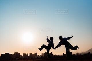 夕日を背景に空中に飛び込む男の写真・画像素材[4167688]