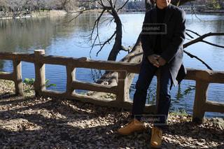 水域の隣のベンチに座っている男の写真・画像素材[2848591]