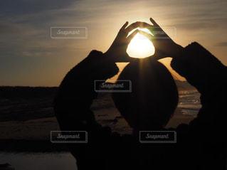 女性,1人,海,空,太陽,後ろ姿,砂浜,夕暮れ,暗い,シルエット,光,逆光,丸,インスタ映え