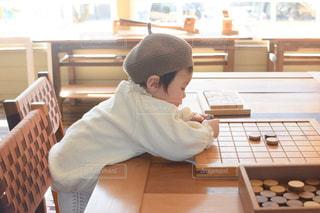 テーブルに座っている小さな男の子の写真・画像素材[3081344]