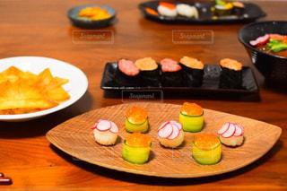 皿に食べ物の皿をトッピングした木製のテーブルの写真・画像素材[3170459]