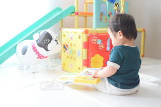 テーブルの上に座っている小さな子供の写真・画像素材[3172025]