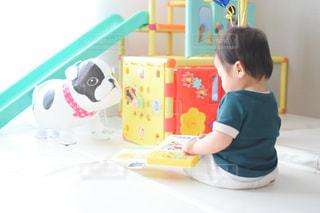 テーブルの上に座っている小さな子供の写真・画像素材[3190103]