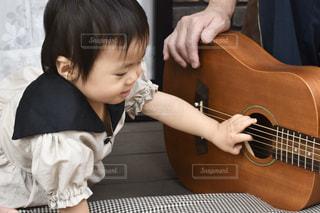 ギターの隣に座っている小さな男の子の写真・画像素材[3201016]