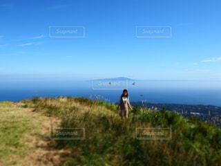 草の多い丘の上に立っている女性の写真・画像素材[3241012]