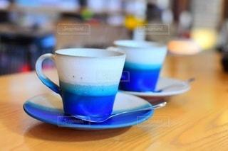 テーブルの上に座っているコーヒーカップのクローズアップの写真・画像素材[3343054]