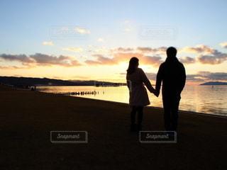 夕日の前に立っている男女の写真・画像素材[3394626]
