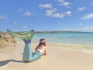 水の体の近くのビーチに座っている人の写真・画像素材[3403817]