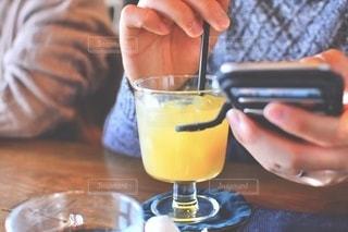 オレンジジュースをグラスでテーブルに座っている人の写真・画像素材[3491708]