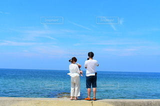 海の隣の砂浜の上に立っている男の写真・画像素材[3556065]