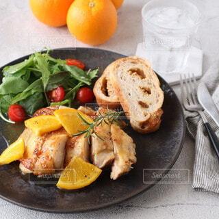 食べ物,食事,朝食,パン,果物,野菜,皿,食器,サラダ,肉,鶏肉,チキンステーキ,主食,オレンジソース