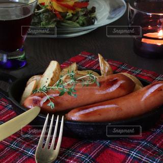 食べ物の皿とビールのグラスをテーブルの上に置くの写真・画像素材[3231301]